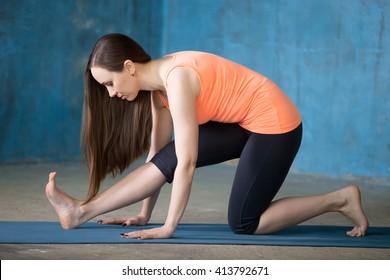 Beautiful young woman dressed in bright sportswear enjoying yoga indoors. Yogi girl working out in grunge interior with blue wall. Ardha Hanumanasana (Half Monkey God Posture). Full length