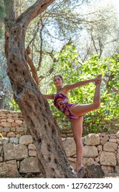 Beautiful, young woman dressed in colorful swim suit practicing yoga in nature. Concept: healthy life, self care, spring resolution, recreation, new beginning, meditation, dancer's pose, self love
