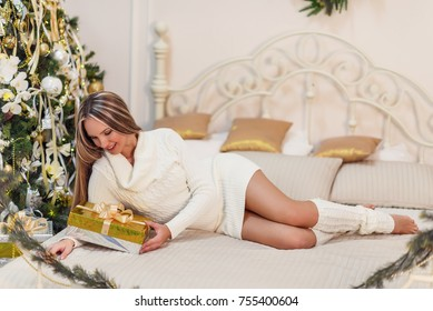 Beautiful young woman dressed in a knitted white sweater and stockings sitting near a New Year tree. Christmas concept. A cozy home portrait. Long hair, slender body.