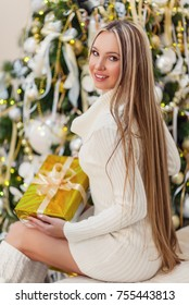 Beautiful young woman dressed in a knitted white sweater and stockings sitting near a New Year tree. Christmas concept. A cozy home portrait. Long hair, slender body