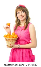 beautiful young woman dressed in a pink dress with a basket full of tangerines
