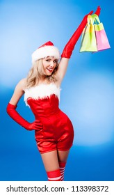 beautiful young woman dressed as Santa, against blue studio background