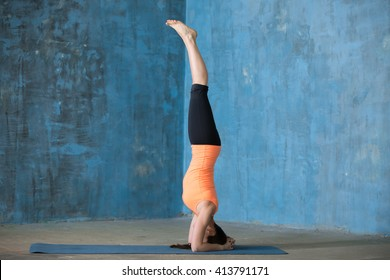 Beautiful young woman dressed in sportswear doing yoga indoors. Yogi girl working out in grunge interior with blue wall. Standing in supported headstand, salamba sirsasana. Full length. Side view
