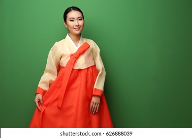 Beautiful young woman dressed in traditional clothing on green background