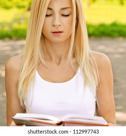 Beautiful young woman dressed in white reading book, against green of summer park.