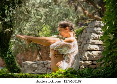 Beautiful young woman dressed in white romantic blouse practicing yoga outdoor in nature. Concept: healthy life, self care, spring resolution, recreation, new beginning, navasana, boat pose