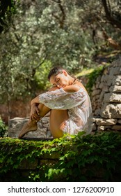 Beautiful, young woman dressed in white romantic blouse practicing yoga outdoor in nature. Concept: healthy life, self care, spring resolution, recreation, new beginning, meditation, hug, self love