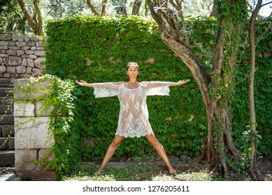 Beautiful, young woman dressed in white romantic blouse practicing yoga in nature. Concept: healthy life, self care, spring resolution, recreation, new beginning, meditation, star pose, self love
