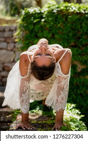 Beautiful, young woman dressed in white romantic blouse practicing yoga in nature. Concept: healthy life, self care, spring resolution, recreation, new beginning, meditation, reverse plank, self love