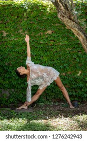 Beautiful, young woman dressed in white romantic blouse practicing yoga in nature. Concept: healthy life, self care, spring resolution, recreation, new beginning, meditation, triangle pose, self love