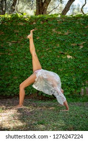 Beautiful, young woman dressed in white romantic blouse practicing yoga in nature. Concept: healthy life, self care, spring resolution, recreation, new beginning, meditation, wheel pose, self love
