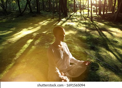 Beautiful young woman dressing in white sits on moss background in zen garden in sunlight. .Meditation is the best way to solve the most complex problems our life