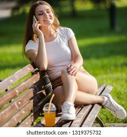 Beautiful young woman drink orange juice, using phone and sitting on bench in the summer park.