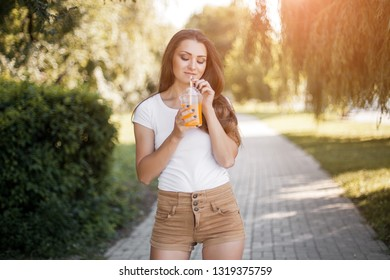Beautiful young woman drink orange juice and walking in summer park.