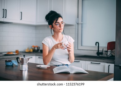 Beautiful young woman drinking coffee in the kitchen