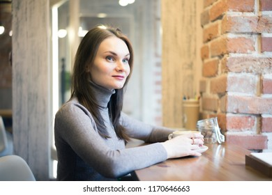Beautiful young woman drinking coffee and looking through window while sitting at a table in a cafe.