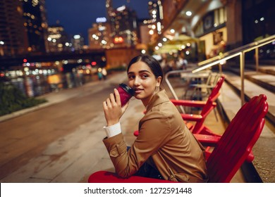 beautiful young woman drinking coffee on Chicago street at night