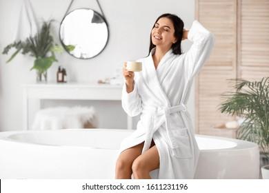 Beautiful young woman drinking coffee in bathroom