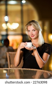 Beautiful young woman drinking coffee in a restaurant
