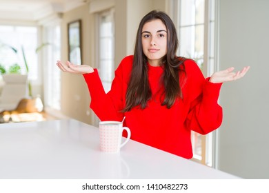 Beautiful young woman drinking a cup of black coffee clueless and confused expression with arms and hands raised. Doubt concept.