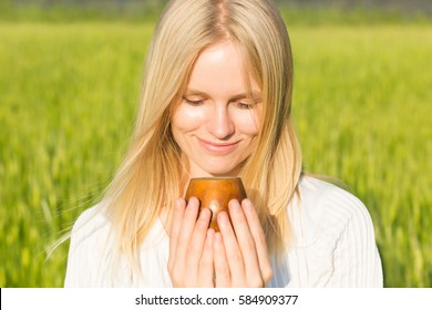 Beautiful young woman drinking fresh tea in a wooden cup outdoors. Summer field Background. Healthcare or Herbal medicine concept.