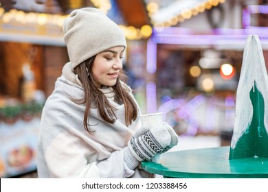 Beautiful young woman drinking hot coffee on the street. Concept Lifestyle, Urban, Winter, Vacation, Happy Christmas, New Year.