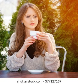 Beautiful young woman drinking hot coffee or tea in the morning at restaurant. Lifestyle photo, girl enjoying her morning coffee in summer garden