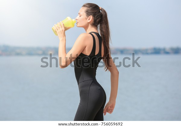 Beautiful young woman drinking protein shake on river bank