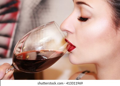 Beautiful young woman drinking red wine