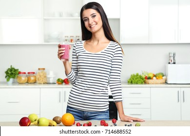 Beautiful young woman drinking smoothie in the kitchen