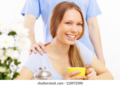 Beautiful young woman drinking tea from yellow cup