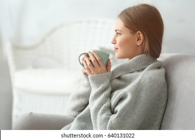 Beautiful young woman drinking tea while resting at home