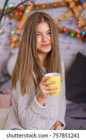 Beautiful young woman drinking tea at the Christmas tree. Beautiful girl celebrates Christmas with cup of cocoa.