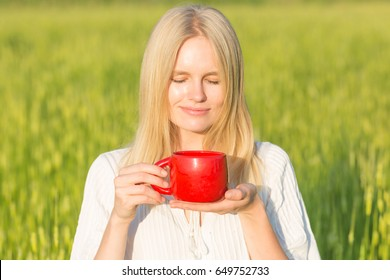 Beautiful young woman drinking tea/coffee outdoors. Green summer field background.
