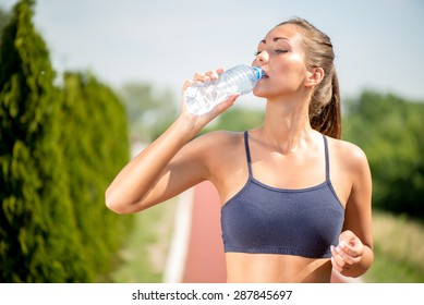 Beautiful young woman drinking water after training