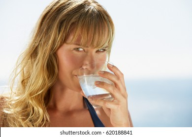 beautiful young woman drinking water in summer beach outdoor