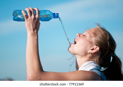 Beautiful young woman drinking water after exercise on sunny summer day