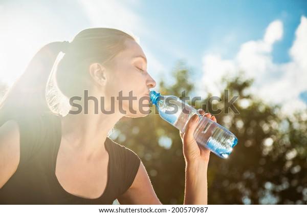 Schöne junge Frauen trinken Wasser nach dem Training
