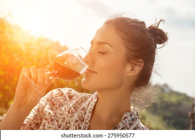 Beautiful Young Woman Drinking Wine In Vineyard
