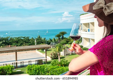 Beautiful young woman is drinking wine on a hotel balcony