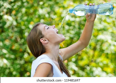 Beautiful young woman drinks water from bottle, against green of summer park.