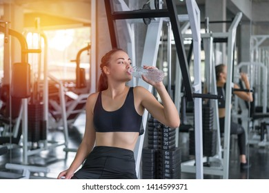 Beautiful young woman drinks water in gym. Sports nutrition concept.