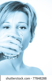 Beautiful young woman drinks water from glass