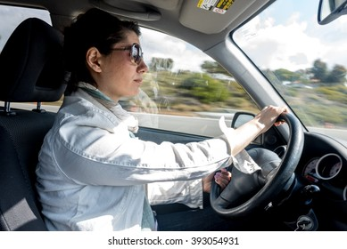 Beautiful young woman driving a car with a motion blured background