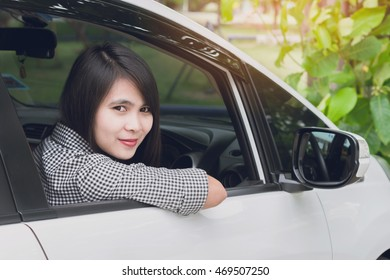 a beautiful young woman driving cars white