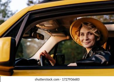 Schöne junge Frau Auto fahren gelb Taxi. Happy Blonde Female Lächeln in Hut Blick auf Kamera. Weiße Girl genießen Komfortable Auto-Reise auf dem Fahrersitz sitzen. Sommerreisekonzept