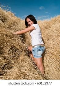 beautiful young woman at a dry haystack