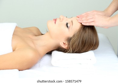Beautiful young woman during facial massage in cosmetic salon close up