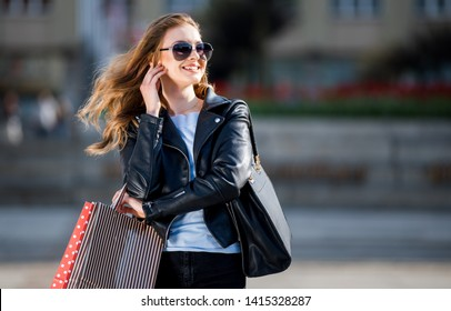 Beautiful young woman during shopping in city looking at something to the side, copy space