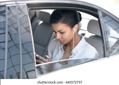 Beautiful young woman in earphones sitting in car and using smartphone